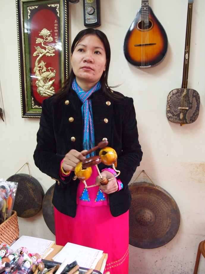 a woman demonstrates a Vietnamese musical instrument