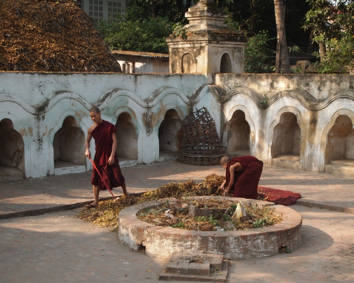 monks sweeping leaves at a pagoda in Amarapura
